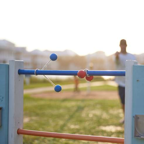 A blue ladder ball wraps around the top wrung next to a red already wrapped around. The man who threw the ladder ball is out of focus in the back