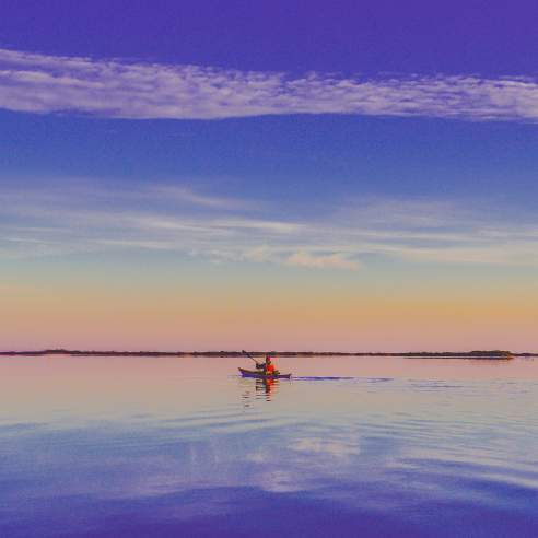 A lone kayaker wearing red floats on calm water that reflects the orange and blue sunrise sky