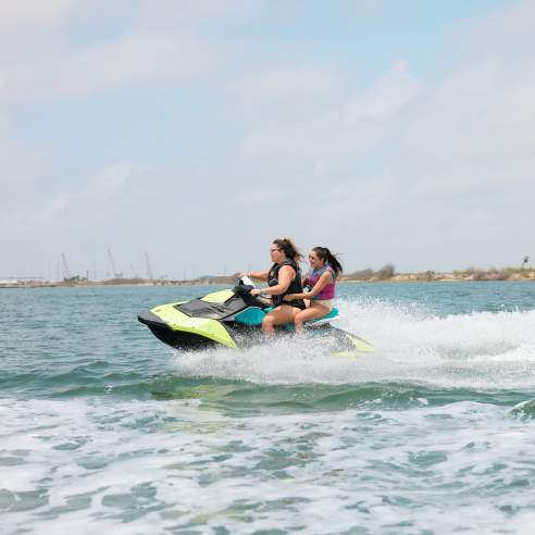 Woman and girl ride on a green jet ski