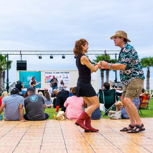 A couple dances on a dance floor in front of groups of people sitting on green grass facing a stage.