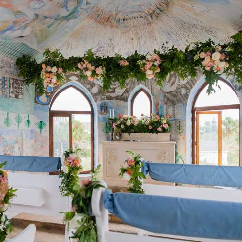 The inside of a small mural-covered chapel is decorated with pink and white flowers and greenery