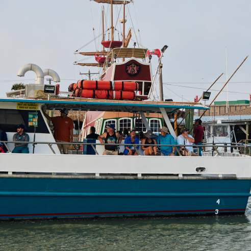 A group sits on a charter boat. Pirate ship is visible in background.