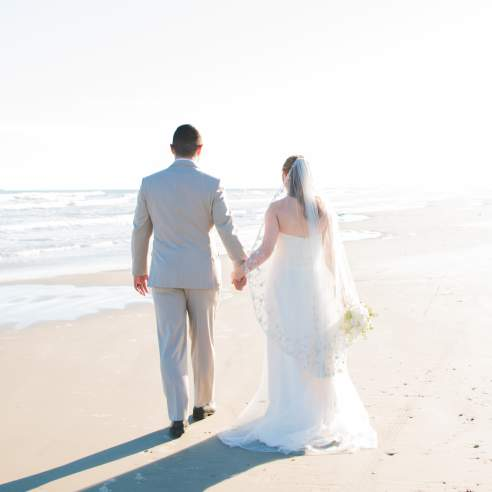 A bride and groom in wedding attire walk hand in hand, backs to the camera, down a light, bright beach