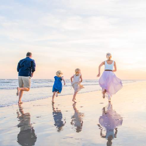A family of four in pastel colors runs on the beach at sunrise