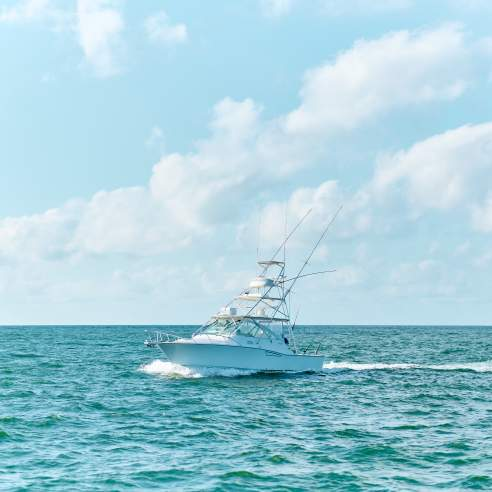 Large white charter boat in turquoise water and bright blue sky