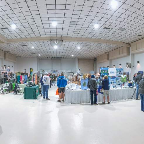 Fish-eye lens photo of an event where booths are set up around a white-walled room