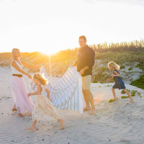 On the beach in front of sand dunes, a mother and father hold a striped blanket between them while two young girls run next to them