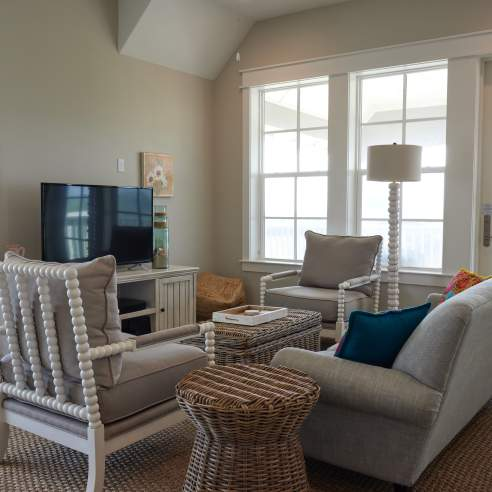 A living room with coastal decor in shades of beige. A tan couch faces a television and two chairs face each other perpendicular to the couch.