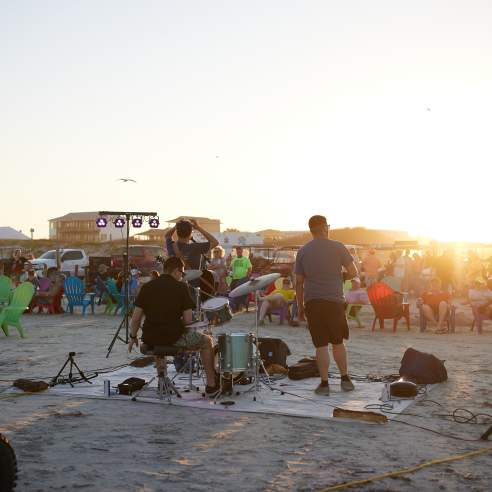 A photo of a three-person band on the beach from behind with a crowd watching from beach chairs