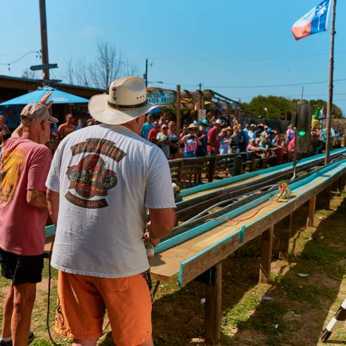 Two men stand in front of narrow wooden racing tracks with belt sanders while a crowd watches