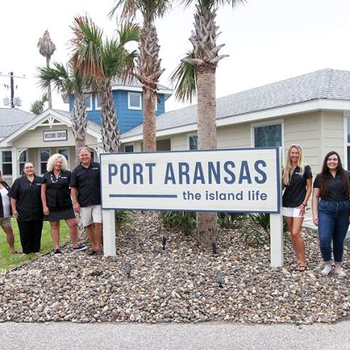 """Seven adults pose in front of a building, around a wooden sign that reads in blue """"Port Aransas the island life"""""""