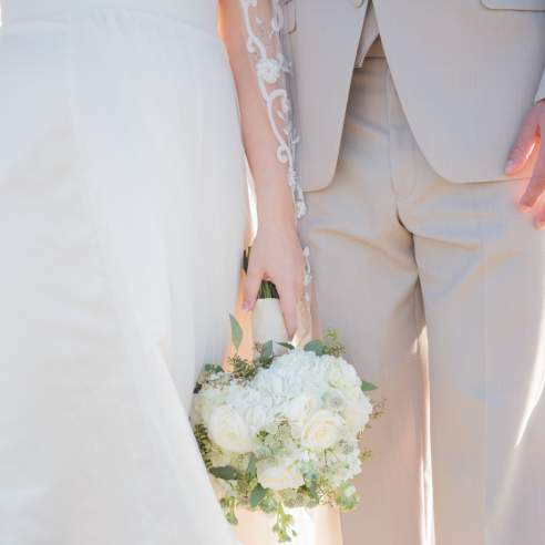 A close-up photo of a couple standing on the beach in wedding attire. The bride holds a bouquet.