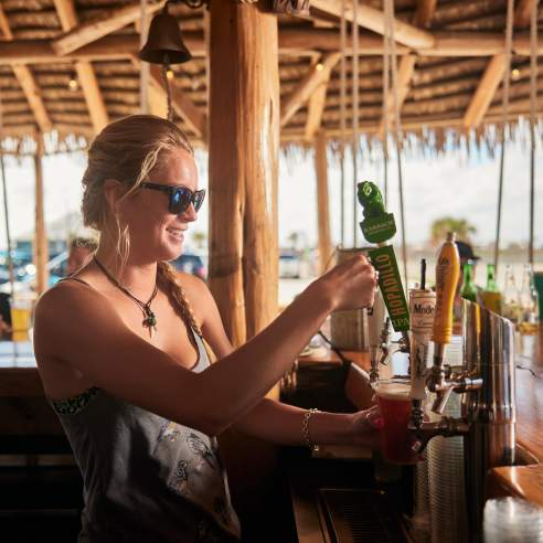 A woman under a tiki hut stands at a bar and pours a beer from tap