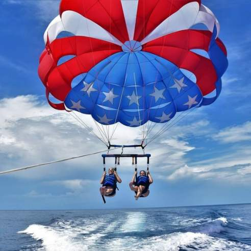 Two people being pulled above the water by a star-spangled parasail