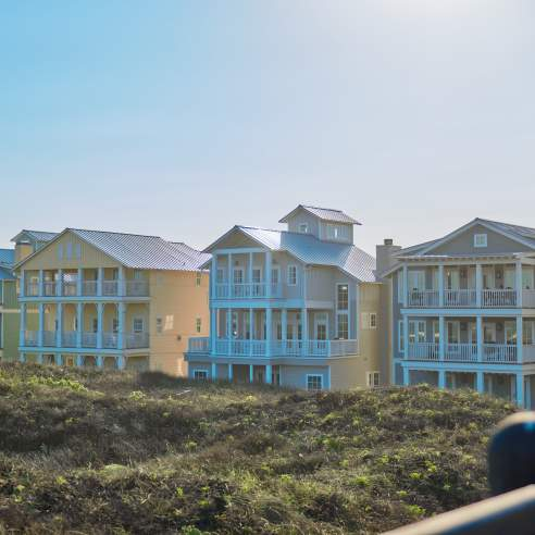 row of 4 large beach houses nestled in dunes in bright sunlight