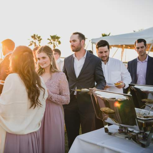 Bridesmaids in mauve dresses and men in suits wait in line at a buffet with palm trees in background