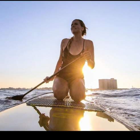 Girl kneels on a stand up paddle board in the water with a paddle in hand.