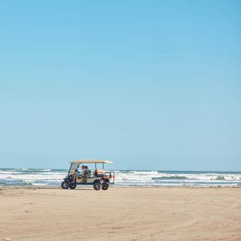 A golf cart sits on the beach in the distance with waves crashing behind.