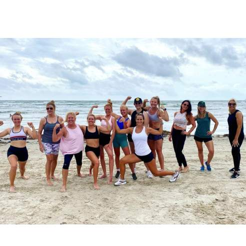 Group of women in workout clothes pose on beach