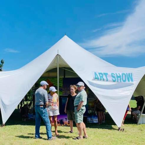 """A white tent is pitched in the middle of a grassy field. The tent has blue text reading """"Art Show."""" A group of four adults stand talking in front of the tent."""