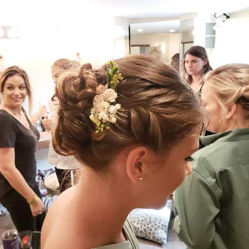 A girl's hairstyle with flowers is in focus with others in background
