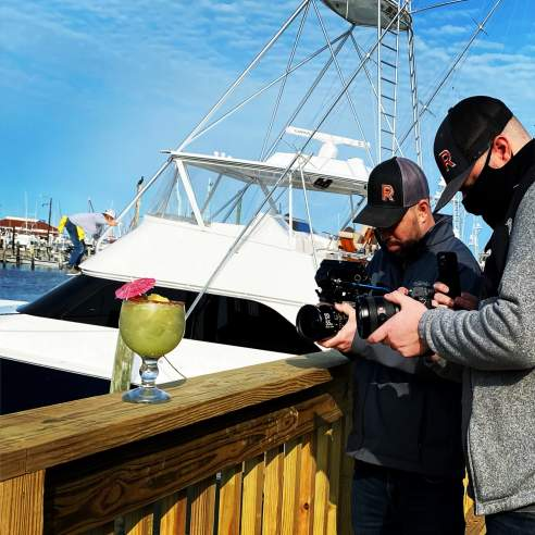 Two men hold large cameras pointed at a tropical margarita on a wooden ledge. A large white yacht is behind them.