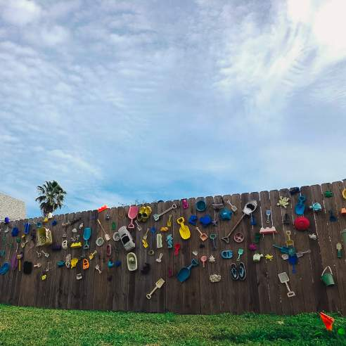 A fence is dotted with colorful discarded beach toys—shovels, cars, buckets, and more. A sky covered in white clouds is above and a house is visible in the left background