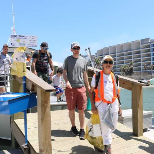 Volunteers step off a boat carrying Up-2-U bags