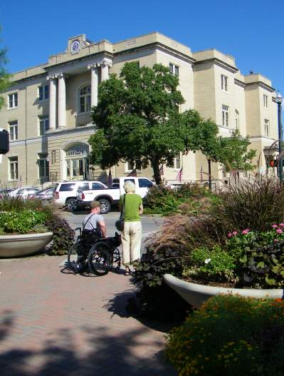 Person standing and person in wheelchair at crosswalk on Louisiana Street