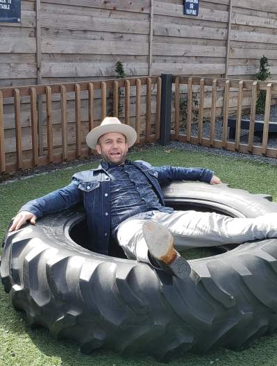 Chet Garner The Daytripper sitting in a tire at The Yard