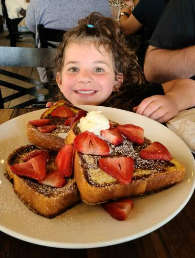 little girl with big plate of french toast covered in strawberries
