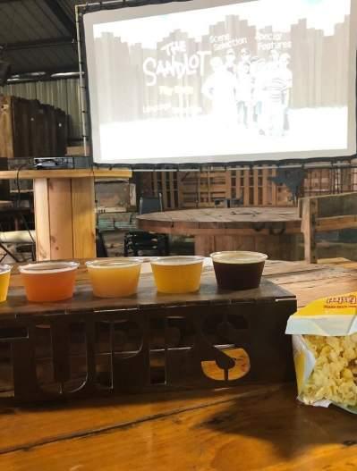 beer flight, bag of popcorn and movie screen at TUPPS