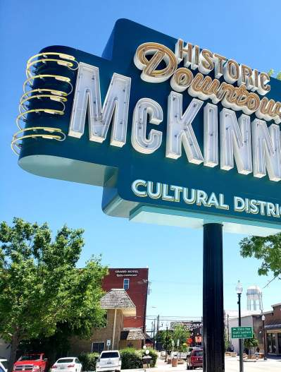 Downtown McKinney Cultural District Sign with blue sky and sidewalk dining