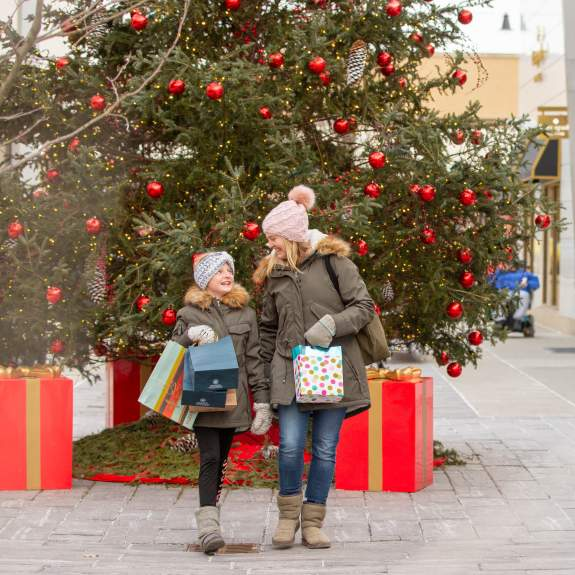 A mom and her daughter stand in front of a Christmas tree with bags of gifts