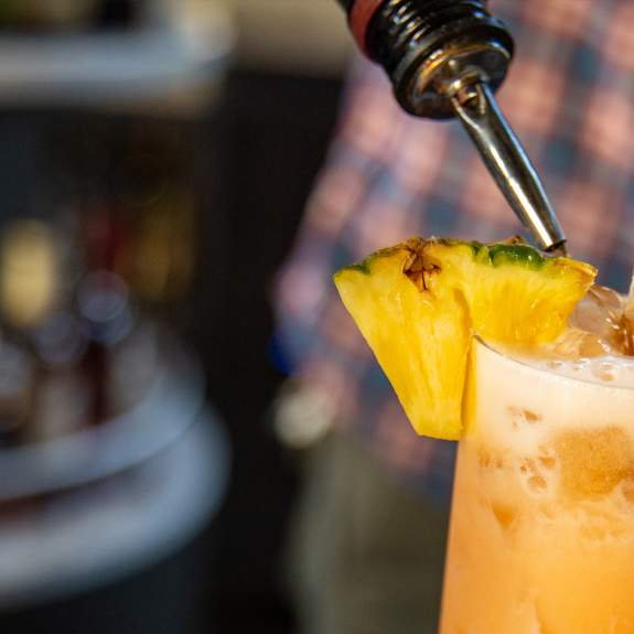A bartender making a tropical cocktail with pineapple garnish