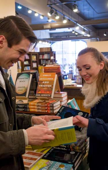 A couple smile as they browse inside a bookstore