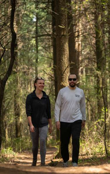 A couple walks along a trail in the woods