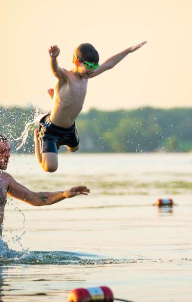 A man and child splash around in the swimming area at Tenney Beach