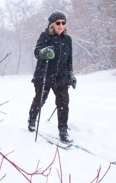 A woman cross country skis as snow falls