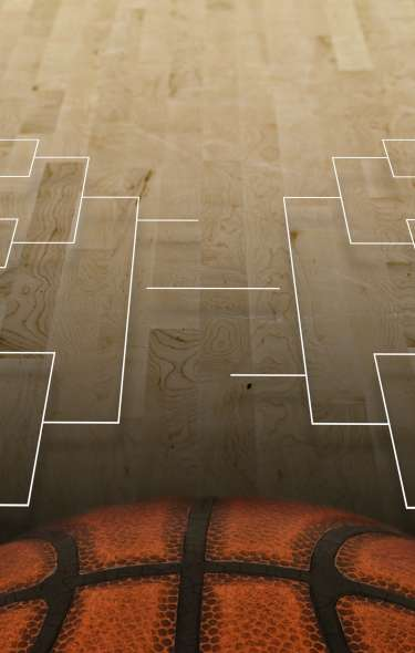 A basketball court floor with a tournament bracket and half of a large basketball on it.