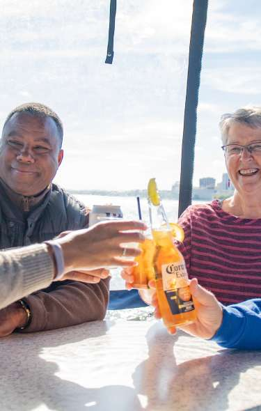 Two couples toast their beverages on board a Betty Lou Cruise
