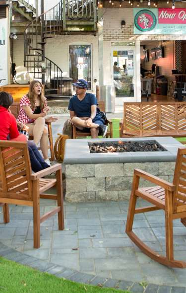 A group of people enjoying ice cream around an outdoor firepit near Chocolate Shoppe