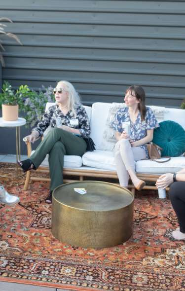 A group of women relax out on a patio