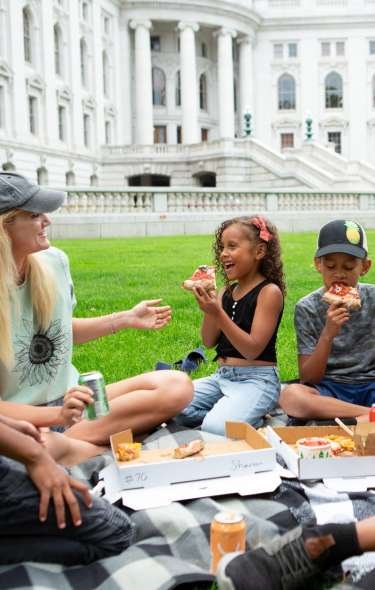 A family enjoys a picnic on the lawn of the Wisconsin State Capitol, one of Madison's most popular attractions