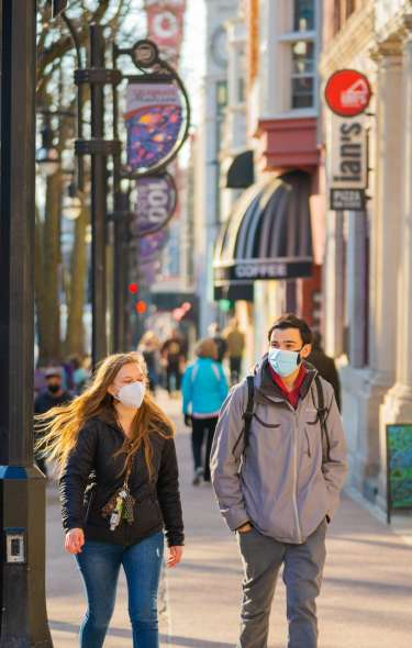 Two people walk together down State Street while wearing face coverings