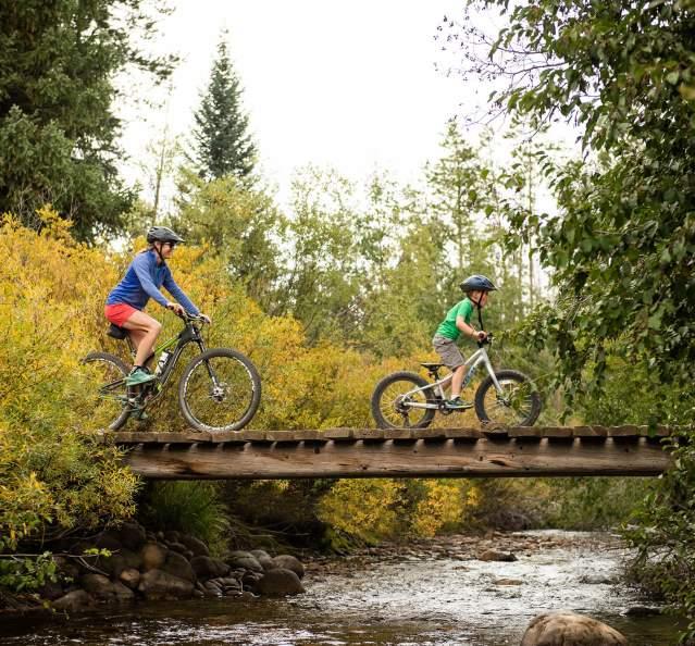 Mom and son biking over a bridge