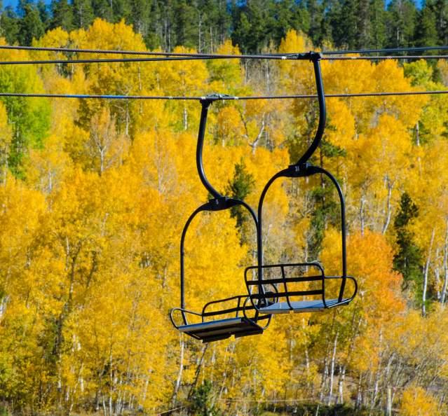 Chairlift in front of golden aspen trees