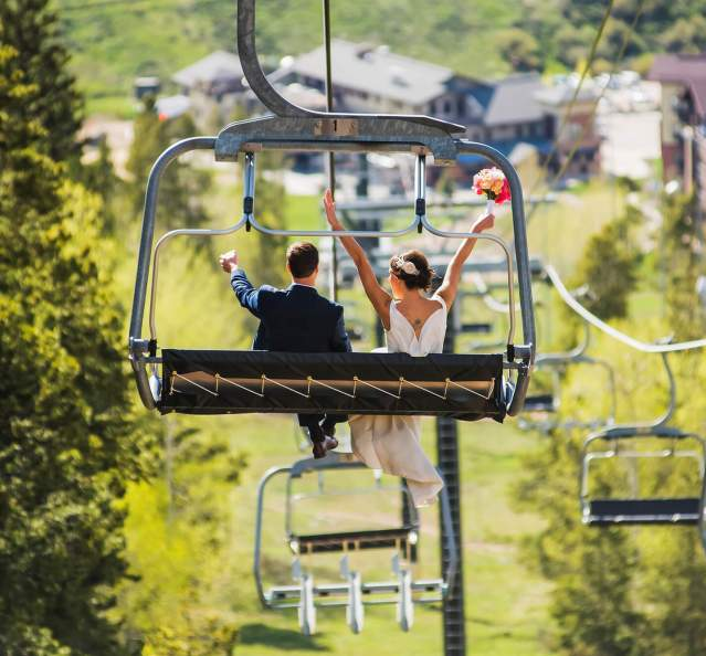 Bride and groom riding a chairlift at their wedding at Granby Ranch
