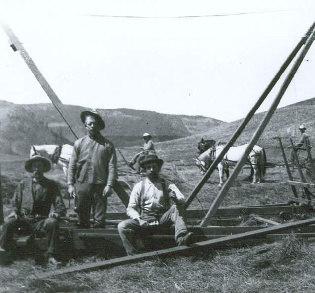 Historic photo of men bailing hay