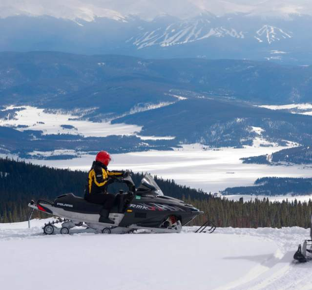 Snowmobiles overlooking Lake Granby and Granby Ranch